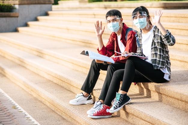 Mannelijke en vrouwelijke studenten met maskers zitten en lezen boeken op de trap