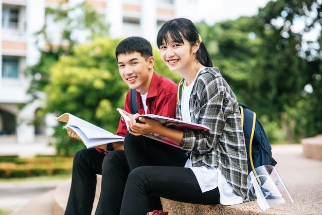 Mannelijke en vrouwelijke studenten zitten en lezen van boeken op de trap.