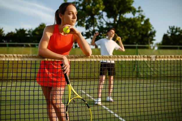 Mannelijke en vrouwelijke tennissers met rackets, training op buitenbaan
