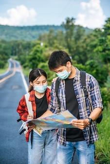 Mannelijke en vrouwelijke toeristen dragen medische maskers en kijken naar de kaart op straat.