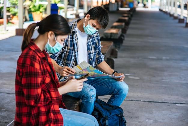 Mannelijke en vrouwelijke toeristen kijken naar de kaart naast de spoorlijn.