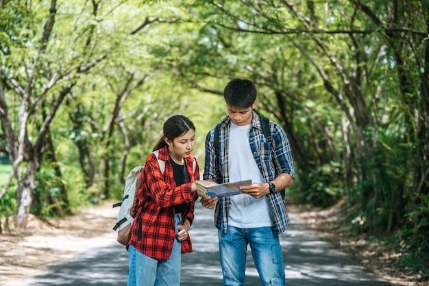 Mannelijke en vrouwelijke toeristen kijken naar de kaart op de weg.