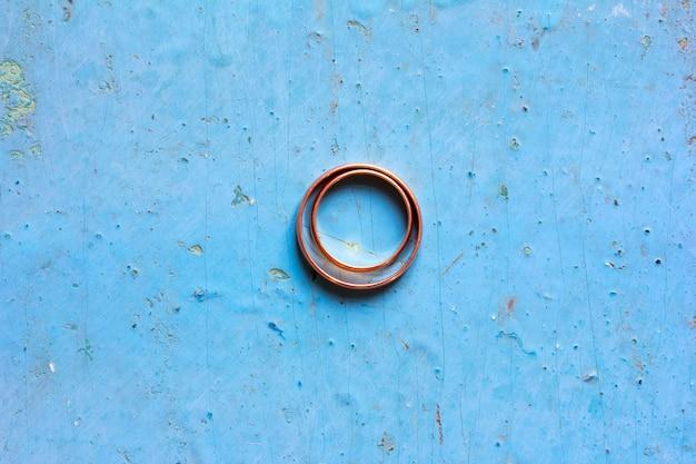 Mannelijke en vrouwelijke trouwringen van goud bij de oude blauwe achtergrond, hoogste mening.