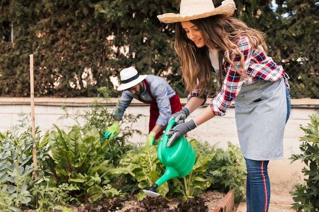 Mannelijke en vrouwelijke tuinman die in de tuin werken