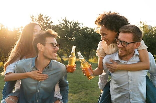Mannelijke en vrouwelijke vrienden die samen buiten tijd doorbrengen en bier drinken