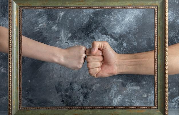 Mannelijke en vrouwelijke vuisten ontmoeten elkaar in het midden van de fotolijst.