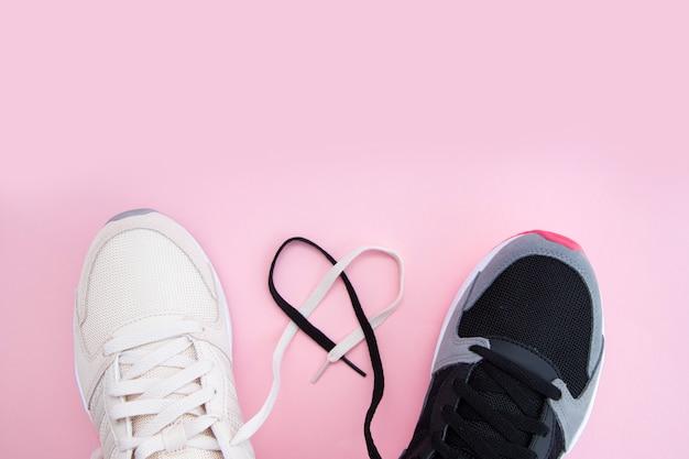 Mannelijke en vrouwelijke witte en zwarte sneakers en veters in de vorm van een hart op een roze achtergrond