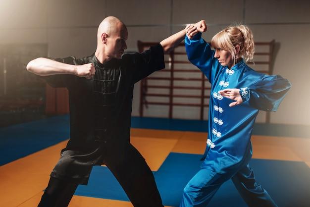 Mannelijke en vrouwelijke wushu-strijders oefenen binnen
