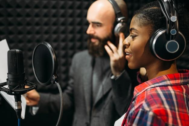 Mannelijke en vrouwelijke zangers in audio-opnamestudio