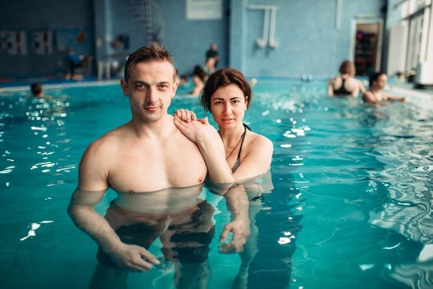 Mannelijke en vrouwelijke zwemmers, vrije tijd in zwembad. aqua-aerobics training, watersport en een gezonde levensstijl