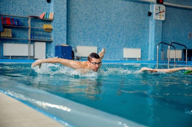 Mannelijke en vrouwelijke zwemmers zwemmen in het zwembad