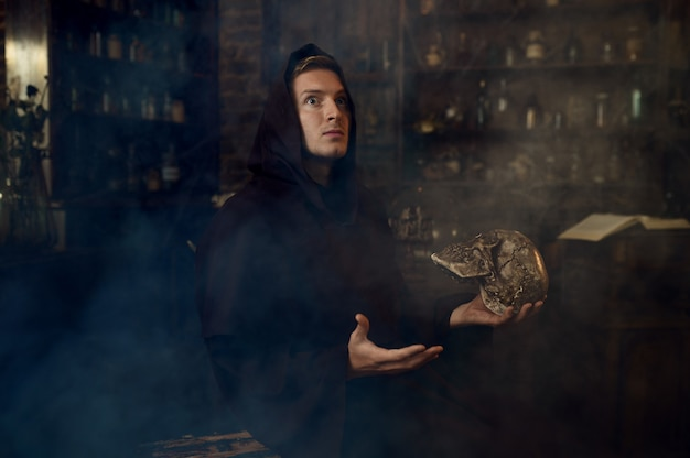 Mannelijke exorcist in zwarte kap houdt menselijke schedel vast. exorcisme, mysterie, paranormaal ritueel, duistere religie, nachthorror, drankjes op de plank