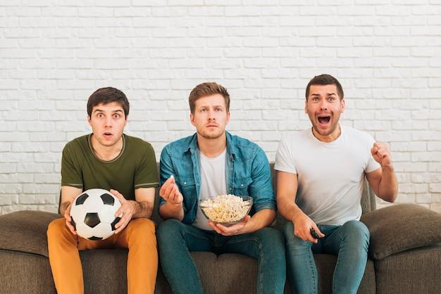 Mannelijke fans die op een voetbalwedstrijd op tv thuis letten