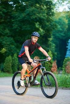 Mannelijke fietser berijdende fiets onderaan park bedekte steeg
