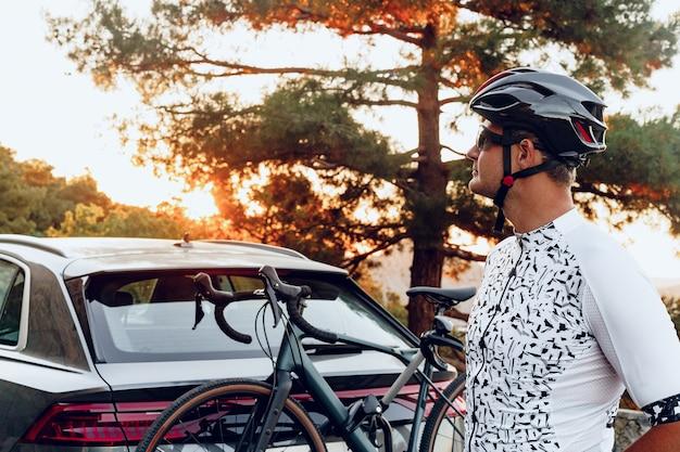 Mannelijke fietser die zijn fiets laadt op een rek van zijn crossover-auto na een rit