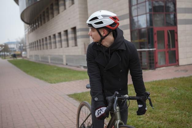 Mannelijke fietser helm dragen, kijken over zijn schouder tijdens het fietsen, kopieer ruimte