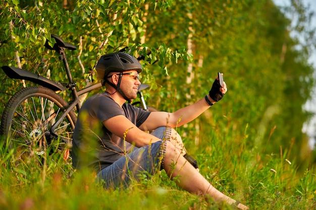 Mannelijke fietser in een helm zit op het gras naast een fiets en neemt een selfie.