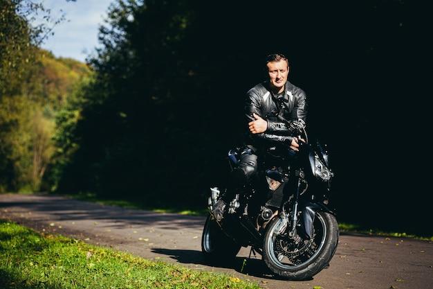 Mannelijke fietser in een zwart leren jas, zittend op een zwarte sportmotorfiets op een bosweg