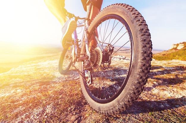 Mannelijke fietser op een mountainbike op een rotsachtig pad bij zonsopgang