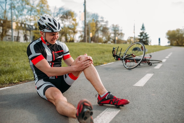 Mannelijke fietser viel van de fiets en raakte zijn knie, fietsend op het fietspad.