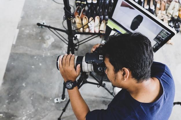 Mannelijke fotograaf die aan studio werkt
