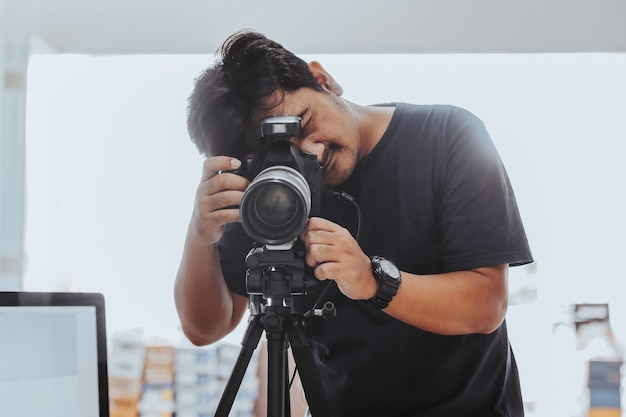 Mannelijke fotograaf die een foto maakt met een statief