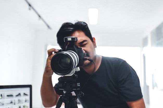 Mannelijke fotograaf die een foto maakt met zijn camera en statief