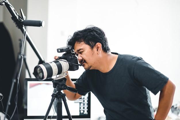 Mannelijke fotograaf die foto's maakt met zijn camera en statief met een monitor en lichtstatief