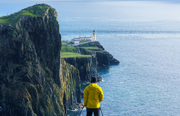 Mannelijke fotograaf die foto's maakt van neist point lighthouse, een van de meest populaire locaties voor fotografie op het eiland skye, schotland, verenigd koninkrijk