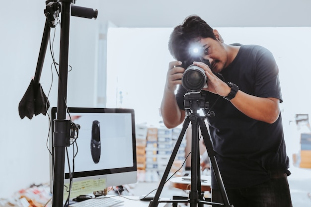 Mannelijke fotograaf die in studio fotografeert met statiefmonitor en lichtstandaard ernaast