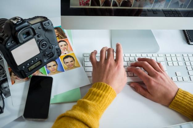 Mannelijke fotograaf die over computer bij bureau werkt