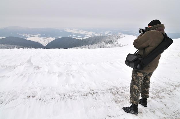 Mannelijke fotograaf maakt foto bovenop de berg