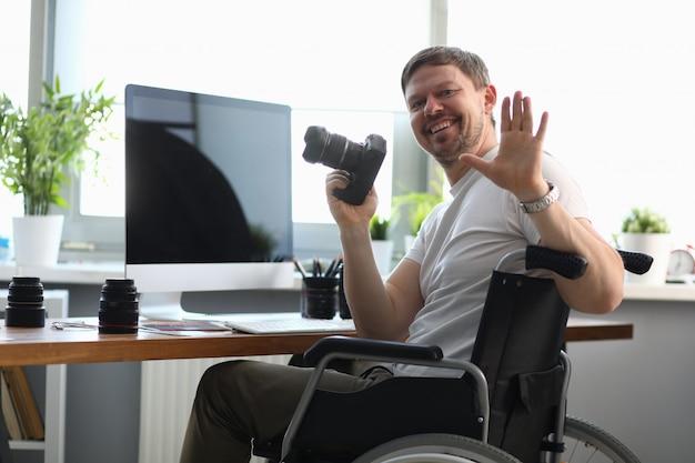 Mannelijke fotograafzitting op rolstoel bij lijst