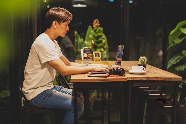 Mannelijke freelancer die aan laptop bij late nacht in koffiewinkel werken.