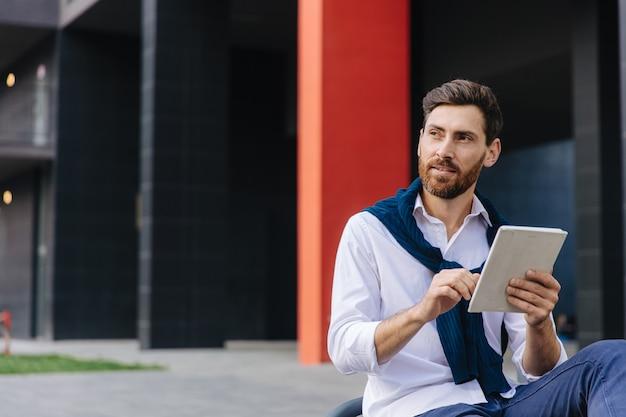 Mannelijke freelancer in wit overhemd die aan digitale tablet werkt terwijl hij buiten zit. jonge, bebaarde man met behulp van moderne gadget zittend op een houten bankje.