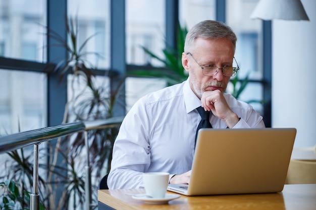 Mannelijke freelancer werkt in een café aan een nieuw zakelijk project. zit aan een groot raam aan de tafel. kijkt naar een laptopscherm met een kopje koffie