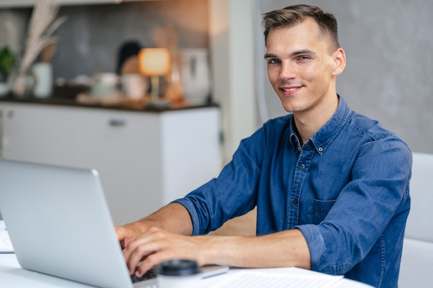 Mannelijke freelancer werkt op een laptop in zijn keuken.