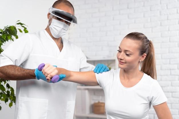 Mannelijke fysiotherapeut die de arm van de vrouw controleert