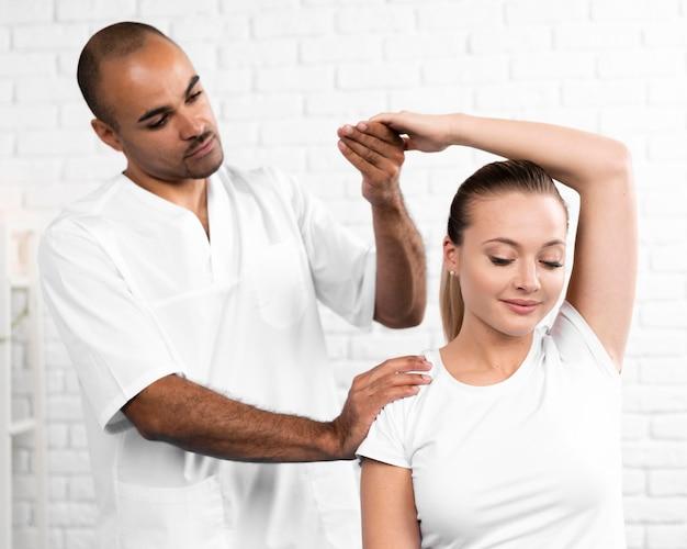Mannelijke fysiotherapeut die de armflexibiliteit van de vrouw controleert
