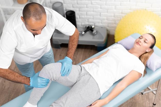 Mannelijke fysiotherapeut die de knie van de vrouw controleert