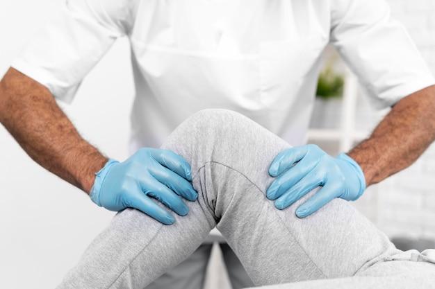 Mannelijke fysiotherapeut die de mobiliteit van de knie van de vrouw controleert