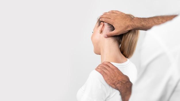 Mannelijke fysiotherapeut die de nekpijn van de vrouw controleert