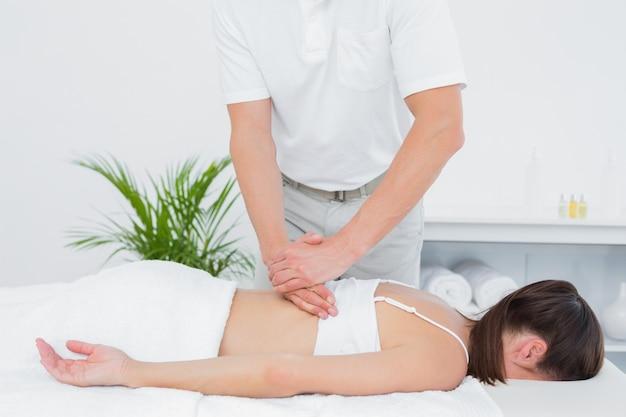 Mannelijke fysiotherapeut die de rug van de vrouw masseren