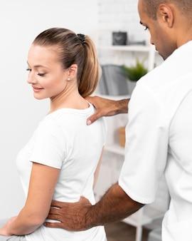 Mannelijke fysiotherapeut die de rugpijn van de vrouw controleert