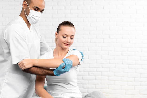 Mannelijke fysiotherapeut die de schouder van de vrouw met exemplaarruimte controleert
