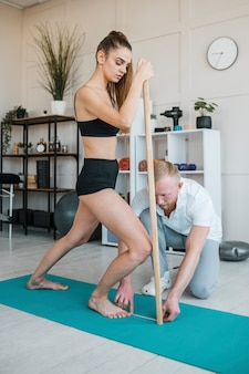 Mannelijke fysiotherapeut die de sterkte van de vrouwelijke patiënt controleert met een houten stok