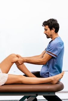 Mannelijke fysiotherapeut die een massage geeft aan een vrouw die op een brancard ligt