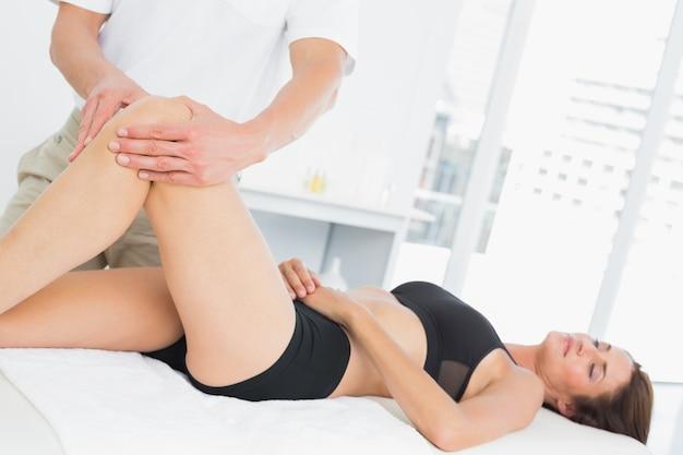 Mannelijke fysiotherapeut die het been van een jonge vrouw onderzoeken