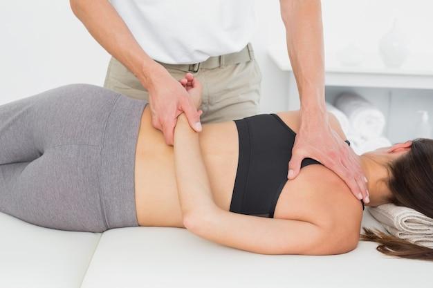 Mannelijke fysiotherapeut die het lichaam van de vrouw masseren