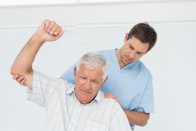 Mannelijke fysiotherapeut die hogere mens bijstaan om hand op te heffen